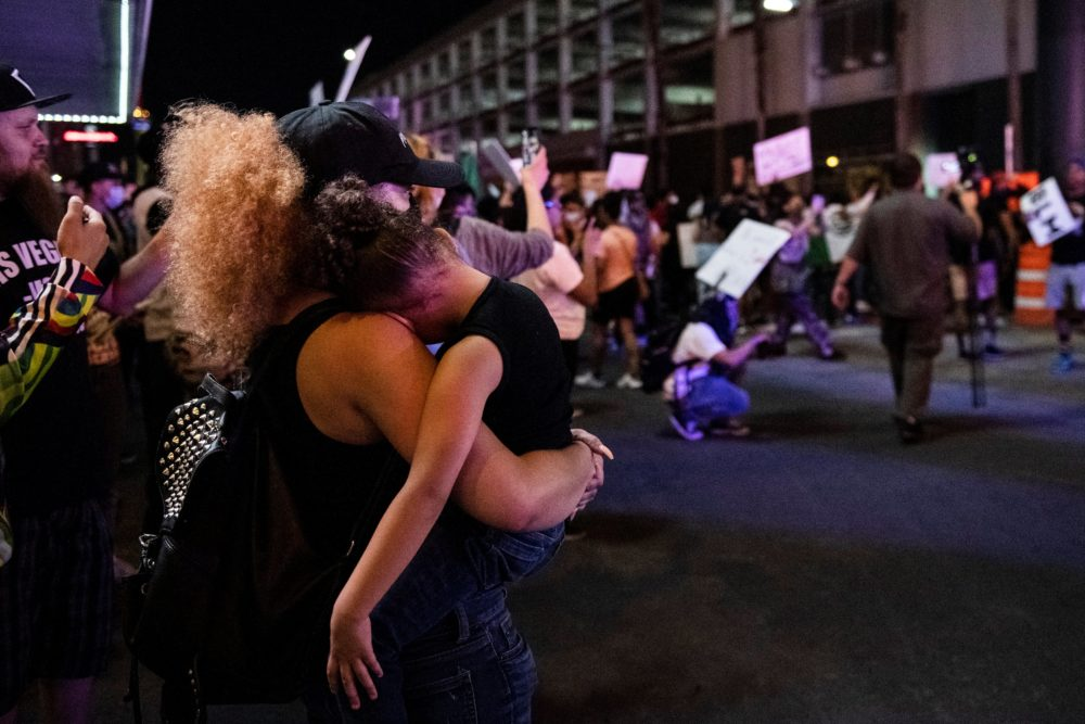 A mother holds her daughter in her arms, on June 1, 2020, in downtown Las Vegas, as she takes part in a Black Lives Matter rally in response to the  death of George Floyd, an unarmed black man who died under the knee of a white Minneapolis police officer. (Bridget Bennett/AFP via Getty Images)