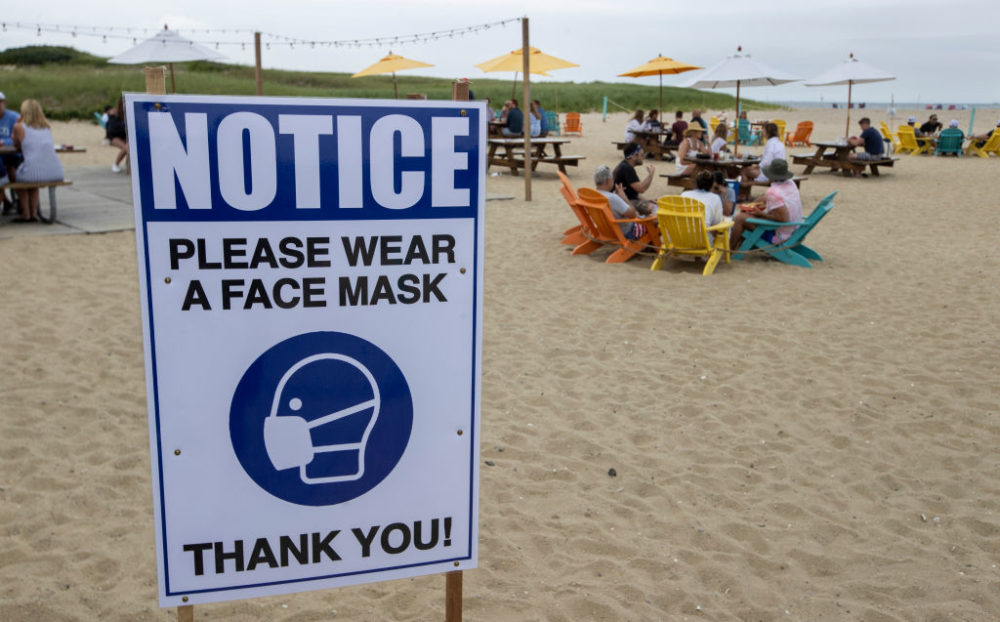 A sign requesting that people wear masks is posted at the Sandbar at Jetties Beach in Nantucket on July 4, 2020. (Photo by Stan Grossfeld/The Boston Globe via Getty Images)