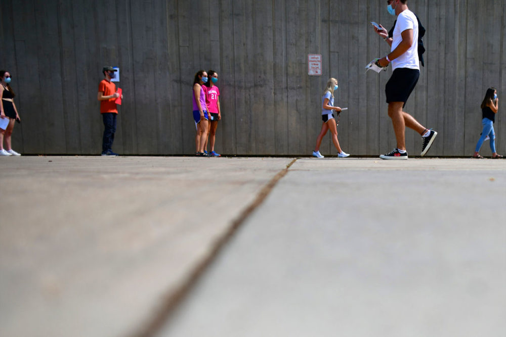 Students wait in line for registration and an identifying wristband after receiving a negative test result for coronavirus while arriving on campus at University of Colorado Boulder on August 18, 2020, in Boulder, Colorado. (Mark Makela/Getty Images)