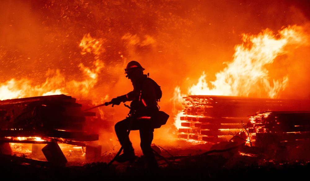 A firefighter douses flames as they push towards homes during the Creek fire in the Cascadel Woods area of unincorporated Madera County, California on September 7, 2020.(JOSH EDELSON/AFP via Getty Images)