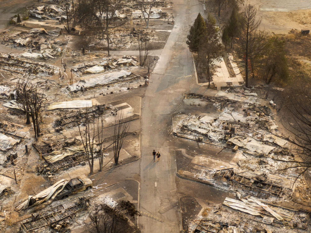 In this aerial view from a drone, people walk through a mobile home park destroyed by fire on September 10, 2020 in Phoenix, Oregon. (David Ryder/Getty Images)