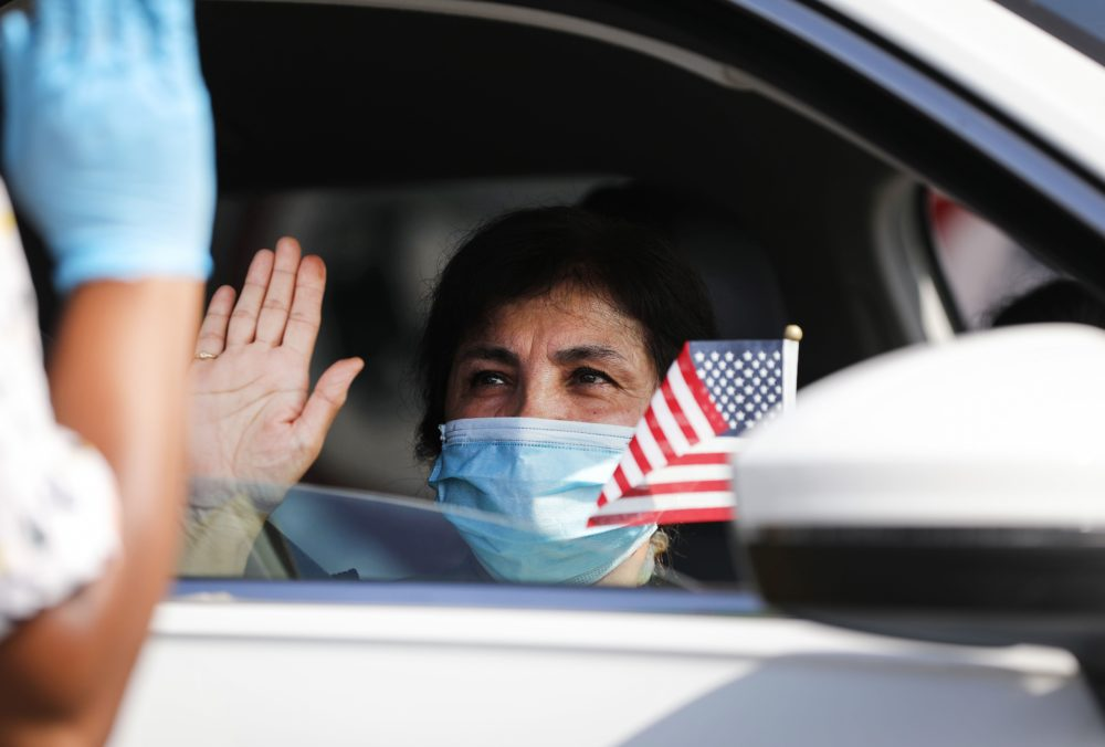 A new U.S. citizen sits in a vehicle while being sworn in by an immigration service officer at a drive-in naturalization ceremony amid the COVID-19 pandemic on July 29, 2020 in Santa Ana, California. (Mario Tama/Getty Images)