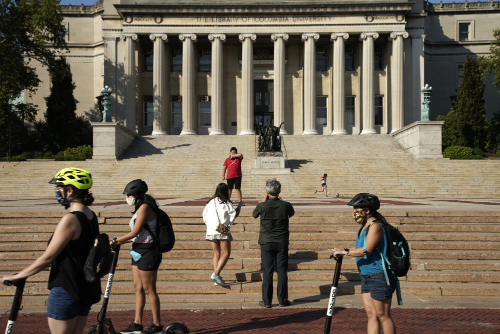 People wearing masks ride electric scooters as visitors take photos in front of Columbia University's Low Memorial Library on August 23, 2020 in New York City.  (John Lamparski/Getty Images)