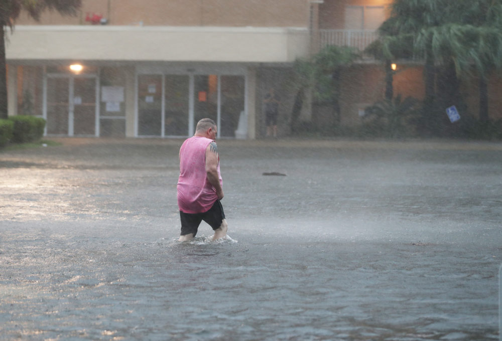 A man walks though a flooded parking lot as the outer bands of Hurricane Sally come ashore on Sept. 15, 2020 in Gulf Shores, Alabama. The storm is bringing heavy rain, high winds and a dangerous storm surge from Louisiana to Florida. (Joe Raedle/Getty Images)