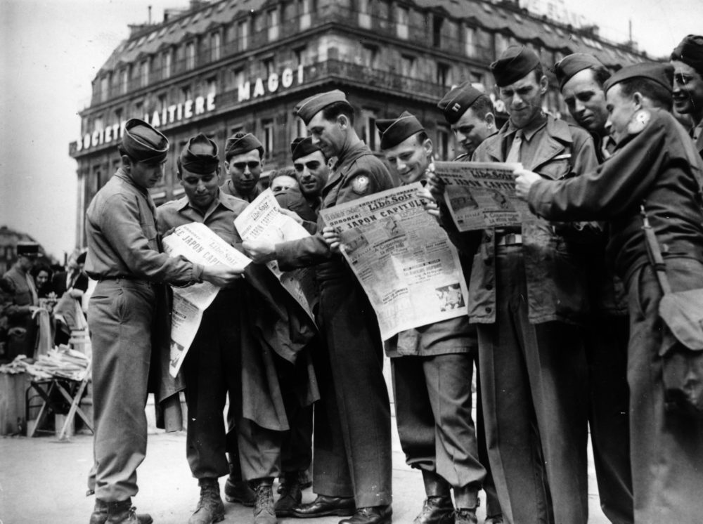 American troops at Place de l' Opera read news of the Japanese surrender in the newspaper in August 1945. (Keystone/Getty Images)