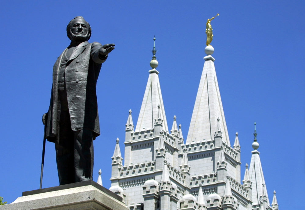 A statue of Brigham Young, second president of the Church of Jesus Christ of Latter Day Saints stands in the center of Salt Lake City with the Mormon Temple spires in the background 19 July 2001. (George Frey/AFP via Getty Images)