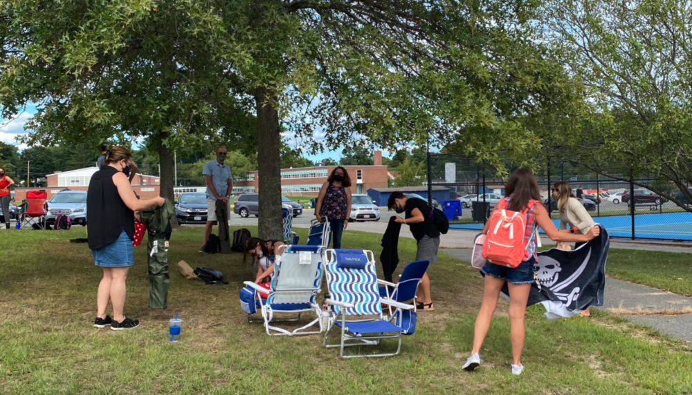 Andover teachers pick up their laptops and lawn chairs to go home after working outside in front of Andover High School on Aug. 31. (Cristela Guerra/WBUR)
