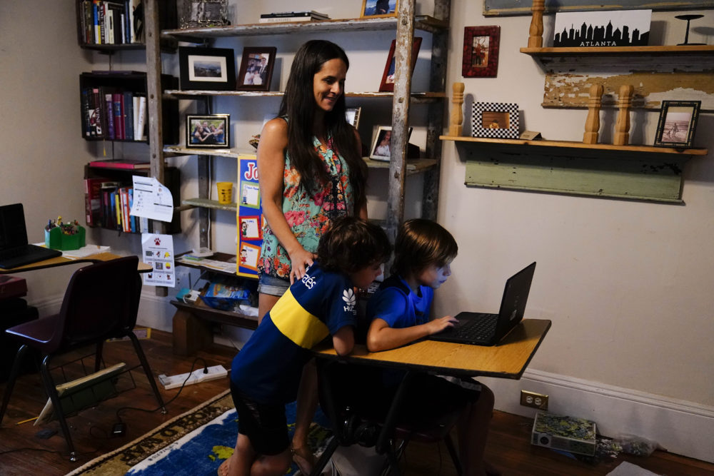 Anna Hamilton, 43, center, is pictured with her sons, Henry, 6, left, and Adrian, 7, right, in their home on Monday, Aug. 24, 2020, in Decatur, Ga. This year, she will help her children with remote schooling. (Brynn Anderson/AP)