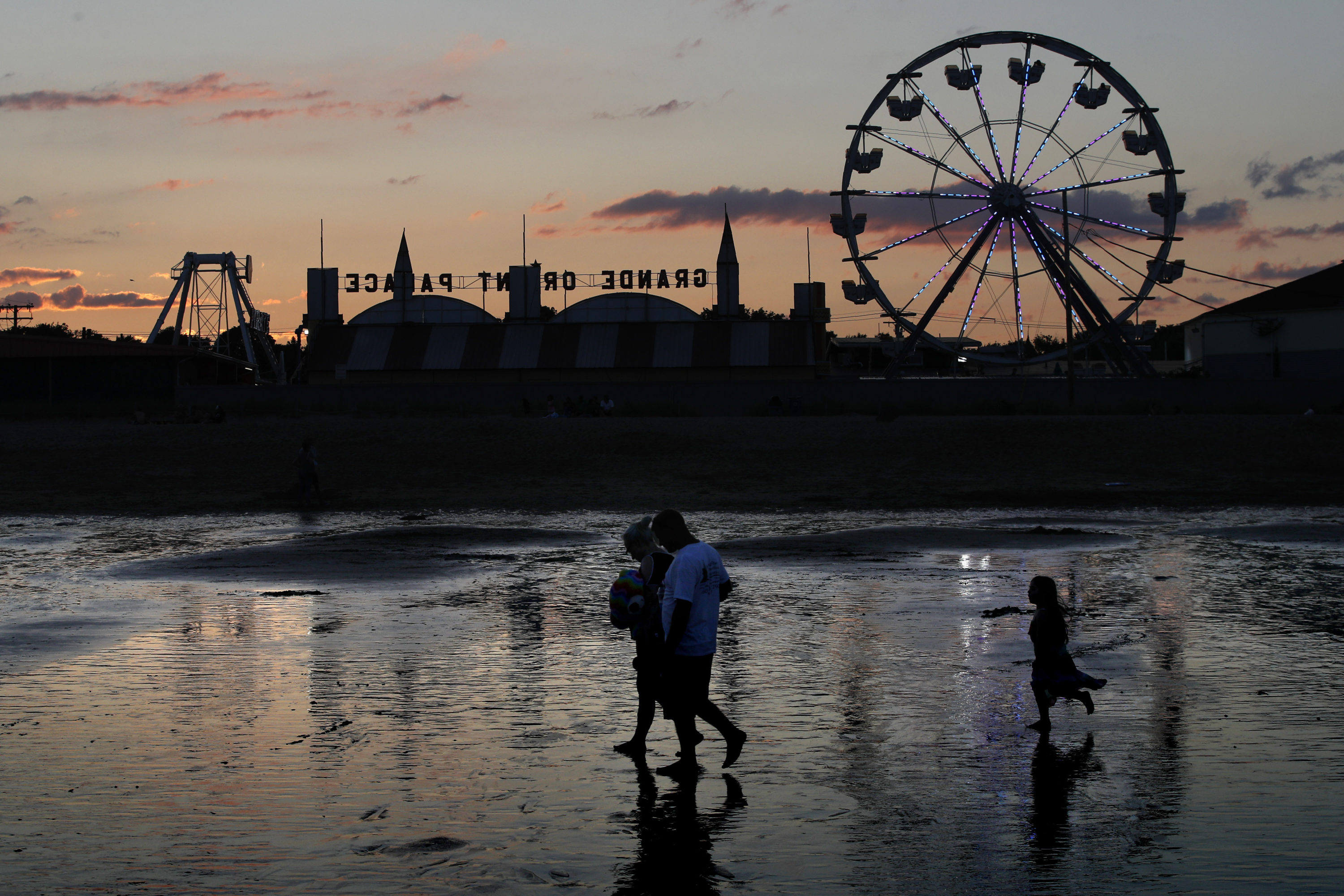 Visitors walk near the Palace Playland amusement park on Aug. 5 at Old Orchard Beach, Maine. (Robert F. Bukaty/AP)