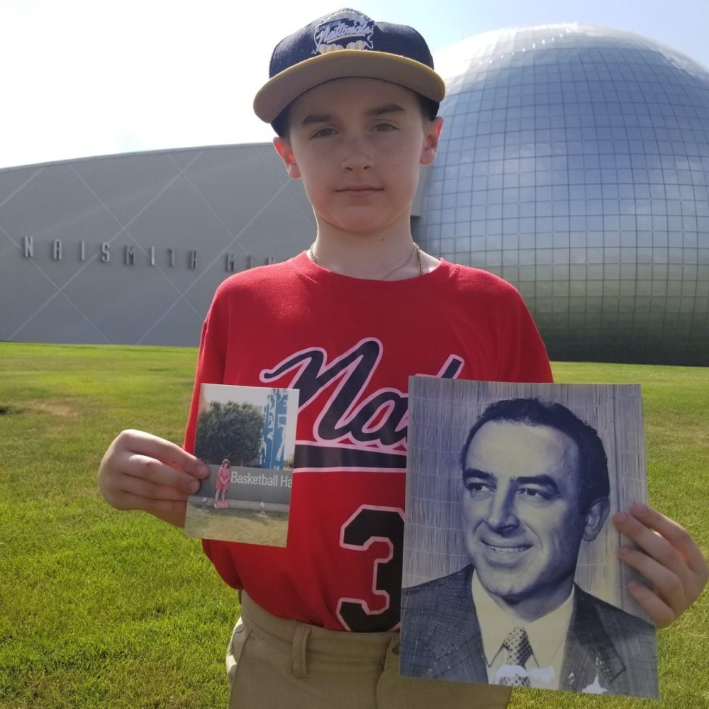 Christian Figueroa's son, Christian, stands on the lawn of the Naismith Hall of Fame holding a photo of Leo Ferris. (Courtesy Christian Figueroa)