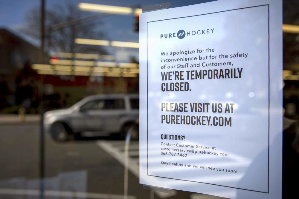 "In this May 13, 2020 photo, Pure Hockey announces on its door in Medford that they're ""temporarily closed"" and urges customers to visit their website. (Robin Lubbock/WBUR)"