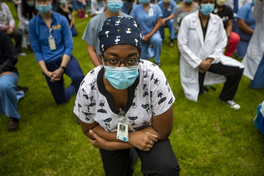 Tracy Charles kneels with hundreds of other staff of the Massachusetts General Hospital participated in a kneel-in, acknowledging the injustice of systemic and individual racism in America, outside the hospital in June. (Jesse Costa/WBUR)