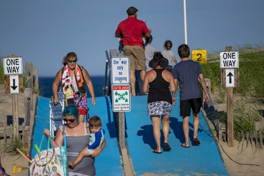Signs and railings are set up to create one way lanes on and off the beach to maintain social distancing at Nauset Beach in Orleans. (Jesse Costa/WBUR)