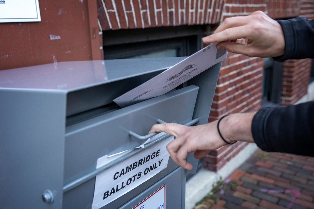 On the eve of Election Day in the Massachusetts primary, a voter places his ballot into the Cambridge drop box. (Robin Lubbock/WBUR)