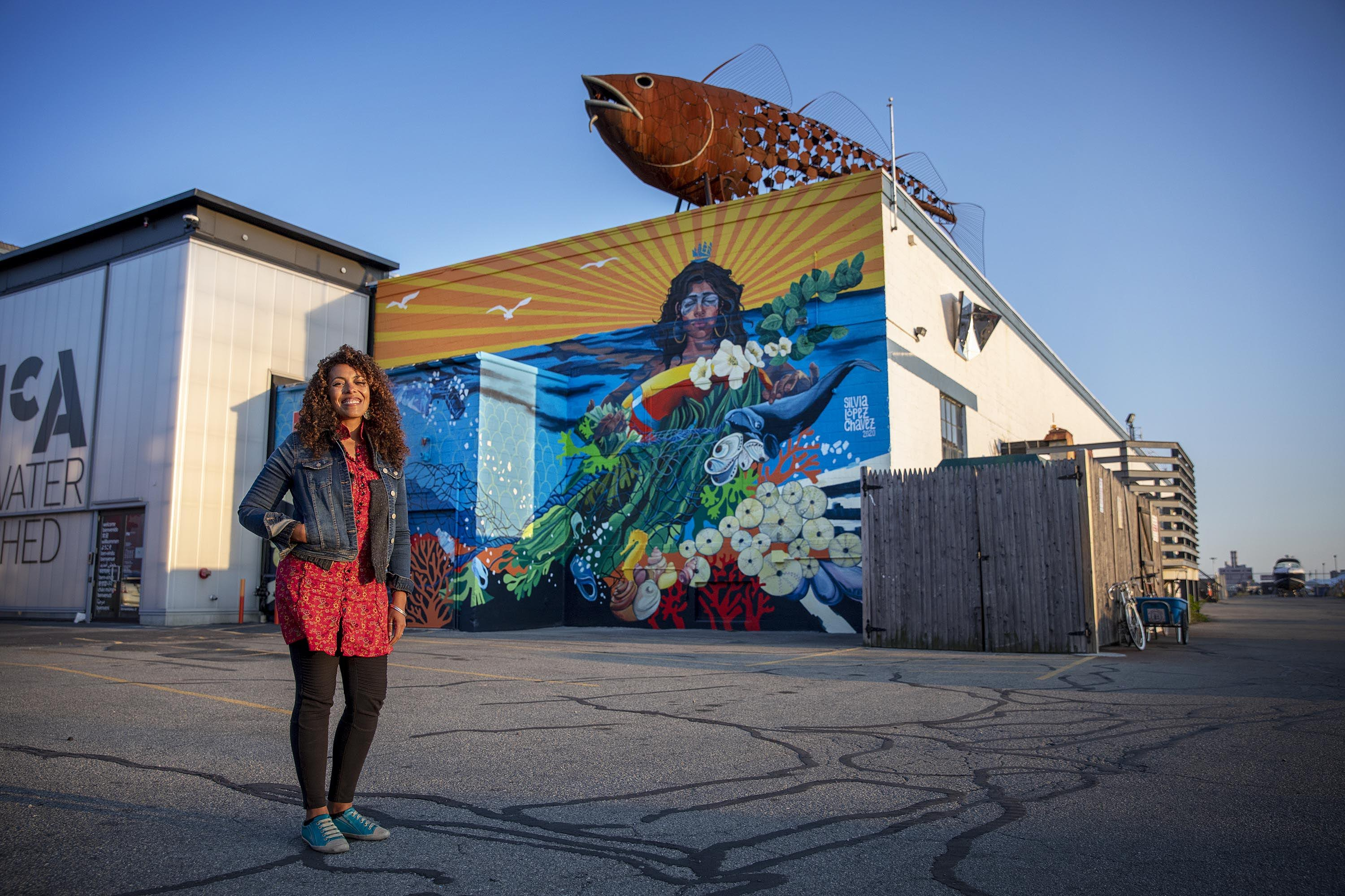 "Artist Silvia López Chavez by her mural ""Rise"" at the Boston Harbor Shipyard and Marina in East Boston. (Robin Lubbock/WBUR)"