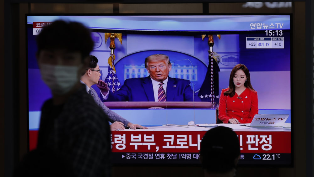 A man wearing a face mask walks near a TV screen reporting about U.S. President Donald Trump and first lady Melania Trump during a news program with a file image of Trump at the Seoul Railway Station in Seoul, South Korea, Friday, Oct. 2, 2020. (Lee Jin-man/AP)