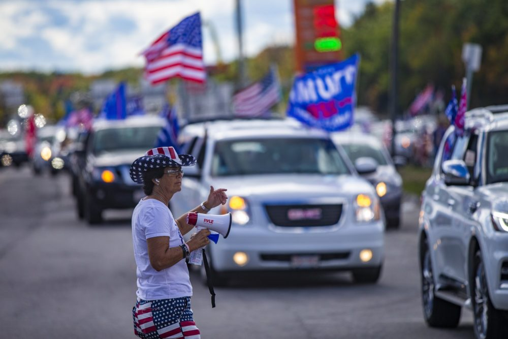 Lorraine Cambria waves cars to leave the Lexington Service Center on Route 95, as they merge with the rest of the caravan to drive to the rally in Londonderry, N. H. (Jesse Costa/WBUR)
