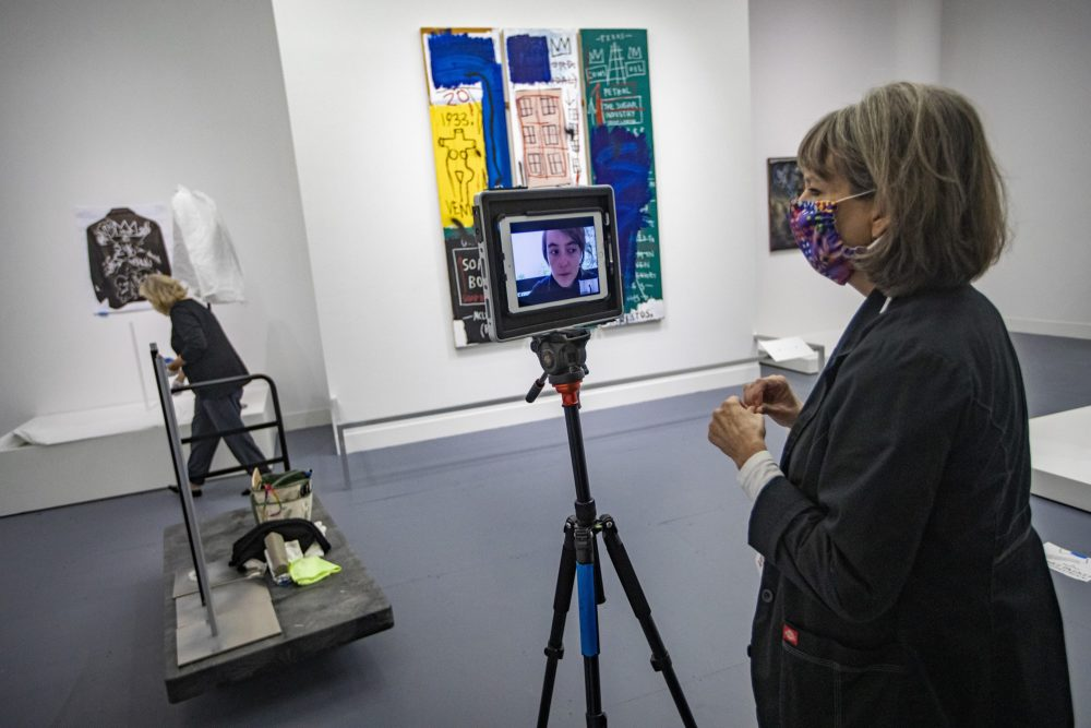 "Head registrar Jill Kennedy-Kernohan on a remote Zoom check-in call with the exhibit's project manager Valentine Lescar assuring pieces in the ""Writing the Future: Basquiat and the Hip-Hop Generation"" exhibit have been properly installed. (Jesse Costa/WBUR)"