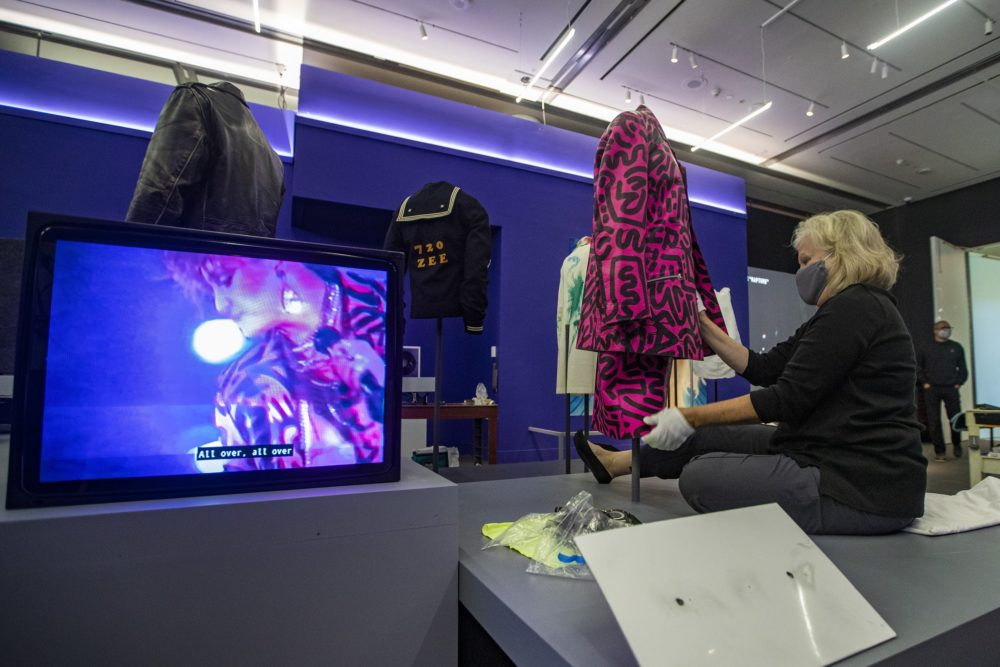 "Meredith Montague, head of textile conservation at the Museum of Fine Arts, Boston, installs ""Decorated Suit"" by Keith Haring and LA2 which was worn by Madonna in 1984, as shown on the video screen. (Jesse Costa/WBUR)"