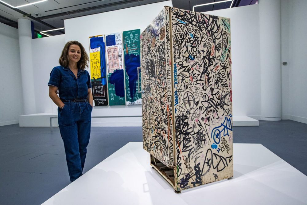 "Liz Munsell, curator of contemporary art at the MFA, stands beside ""Untitled (Fun Fridge)"" by Jean‑Michel Basquiat. (Jesse Costa/WBUR)"