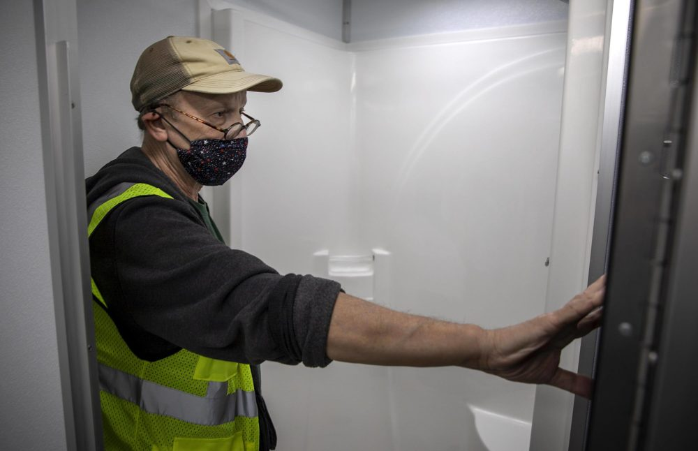 Jim Stewart check over one of the shower stalls in the mobile unit. (Robin Lubbock/WBUR)