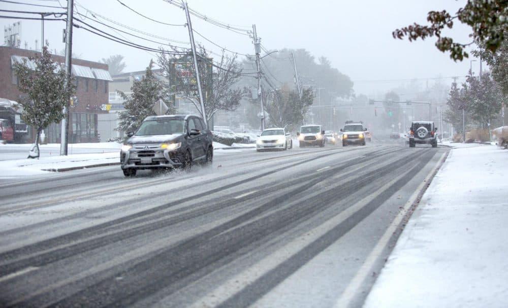 Cars cut tracks through the fresh snow on Waltham Street in Waltham on Friday morning. ( Robin Lubbock/WBUR)