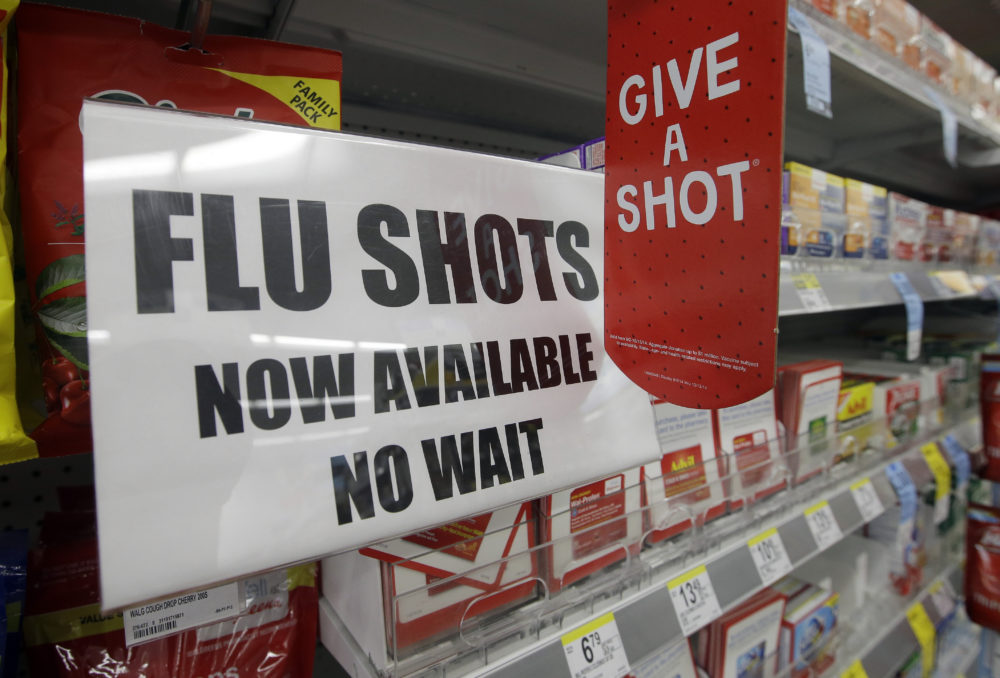 In this Sept. 16, 2014 file photo, a sign telling customers that they can get a flu shot in a Walgreen store is seen in Indianapolis. (Darron Cummings/AP)