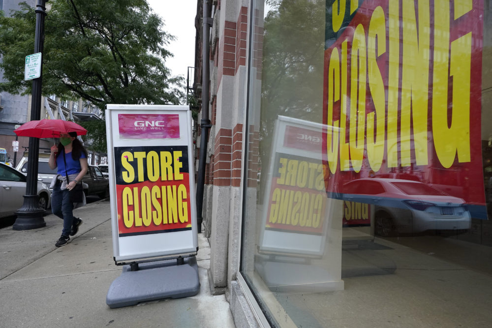 In this Sept. 2, 2020, file photo, a passerby walks past a business storefront with store closing signs in Boston. The U.S. unemployment rate dropped to 7.9% in September, but hiring is slowing and many Americans have given up looking for work, the government said Friday, Oct. 2, in the final jobs report before the voters decide whether to give President Donald Trump another term. (AP Photo/Steven Senne)