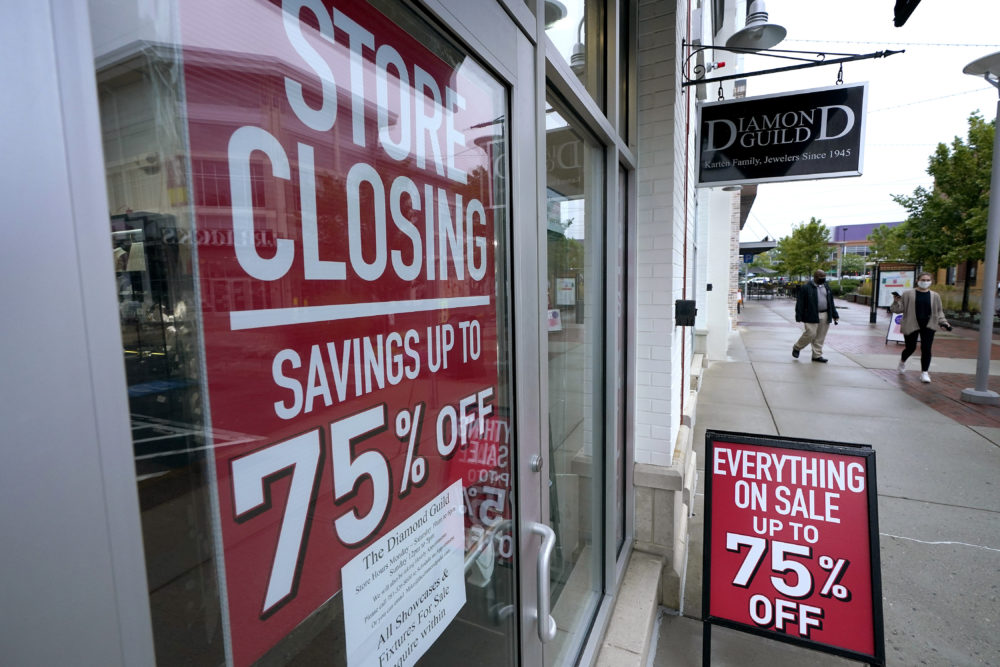 In this Sept. 2, 2020, file photo, passers-by walk past a business storefront with store closing and sale signs in Dedham, Mass. U.S. employers advertised for slightly fewer jobs in August while their hiring ticked up modestly. The Labor Department said Tuesday that the number of U.S. job postings on the last day of August dipped to 6.49 million, down from 6.70 million July. (Steven Senne/AP File)