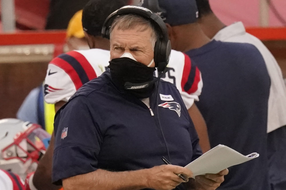 New England Patriots head coach Bill Belichick wears two masks as he watches from the sideline during the first half of an NFL football game against the Kansas City Chiefs, Oct. 5, 2020, in Kansas City. (Charlie Riedel/AP)