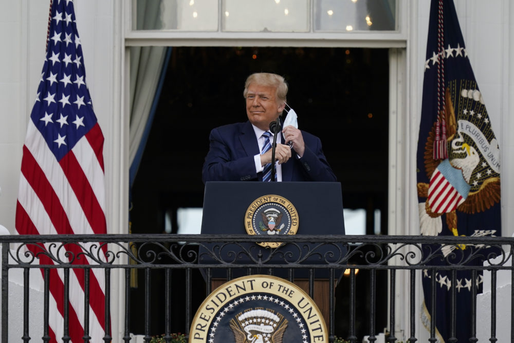 President Donald Trump removes his face mask to speak from the Blue Room Balcony of the White House to a crowd of supporters, Saturday, Oct. 10, 2020, in Washington. (Alex Brandon/AP)