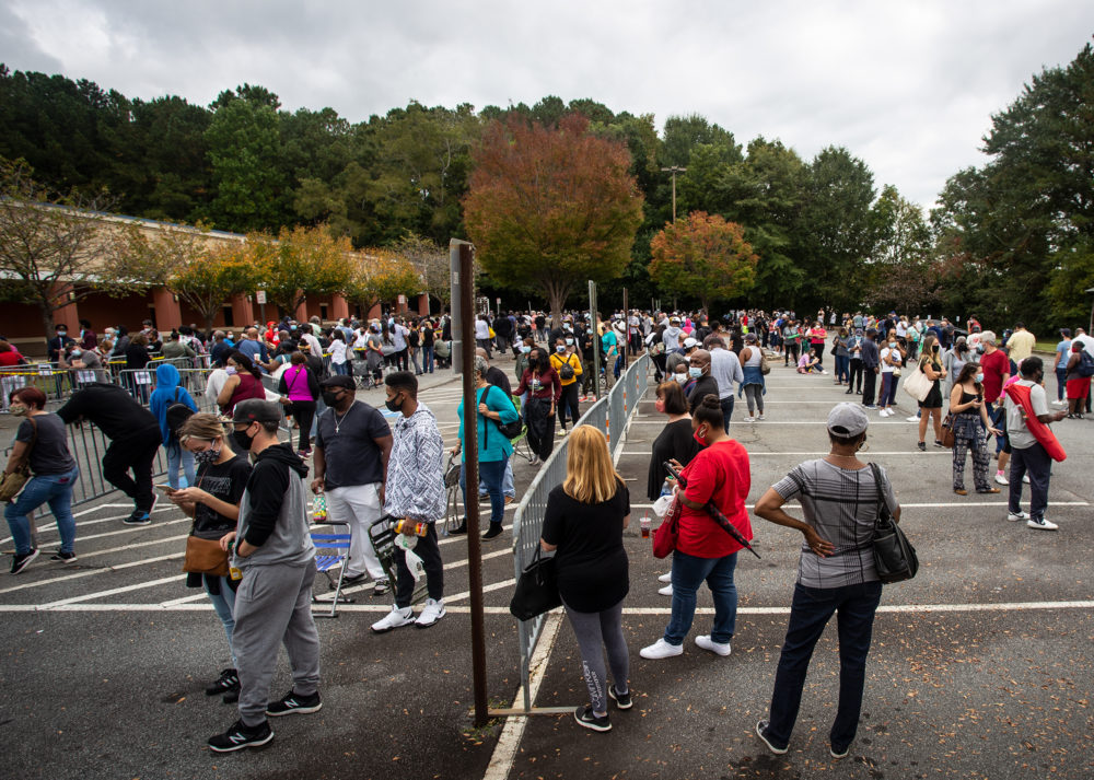 Hundreds of people wait in line for early voting on Monday, Oct. 12, 2020, in Marietta, Georgia. Eager voters have waited six hours or more in the former Republican stronghold of Cobb County, and lines have wrapped around buildings in solidly Democratic DeKalb County. (Ron Harris/AP Photo)