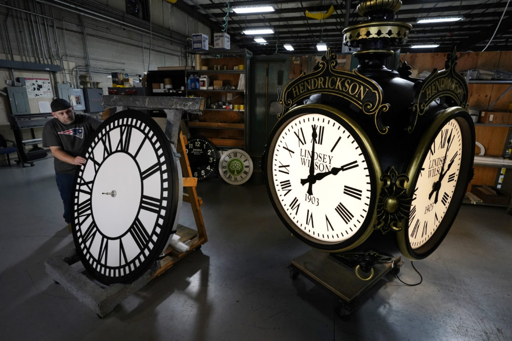 Dan LaMoore rolls a tower clock face across the plant floor at Electric Time Company, Friday, Oct. 23, 2020, in Medfield, Mass. Daylight saving time ends at 2 a.m. local time Sunday, Nov. 1, 2020, when clocks are set back one hour. (Elise Amendola/AP)