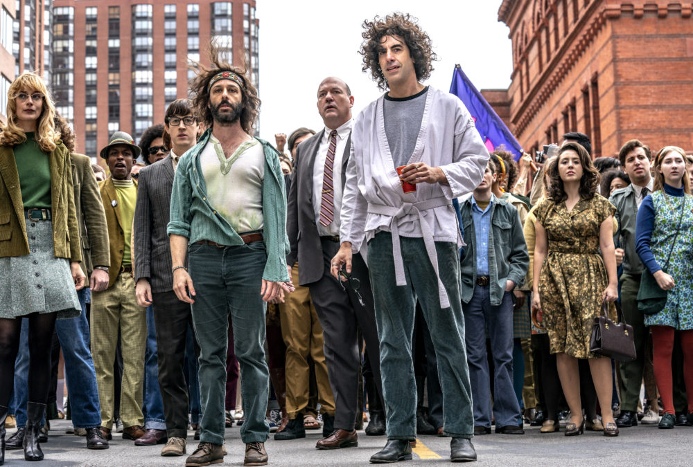 "Left to right: Caitlin Fitzgerald, Alan Metoskie, Alex Sharp, Jeremy Strong, John Carroll Lynch, Sasha Baron Cohen and Noah Robbins in ""The Trial of the Chicago 7."" (Courtesy Niko Tavernise/Netflix)"
