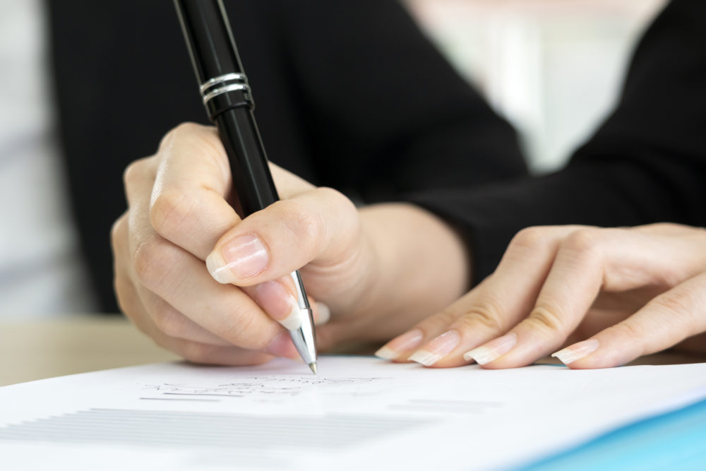 Business woman signing the contract to conclude a deal.