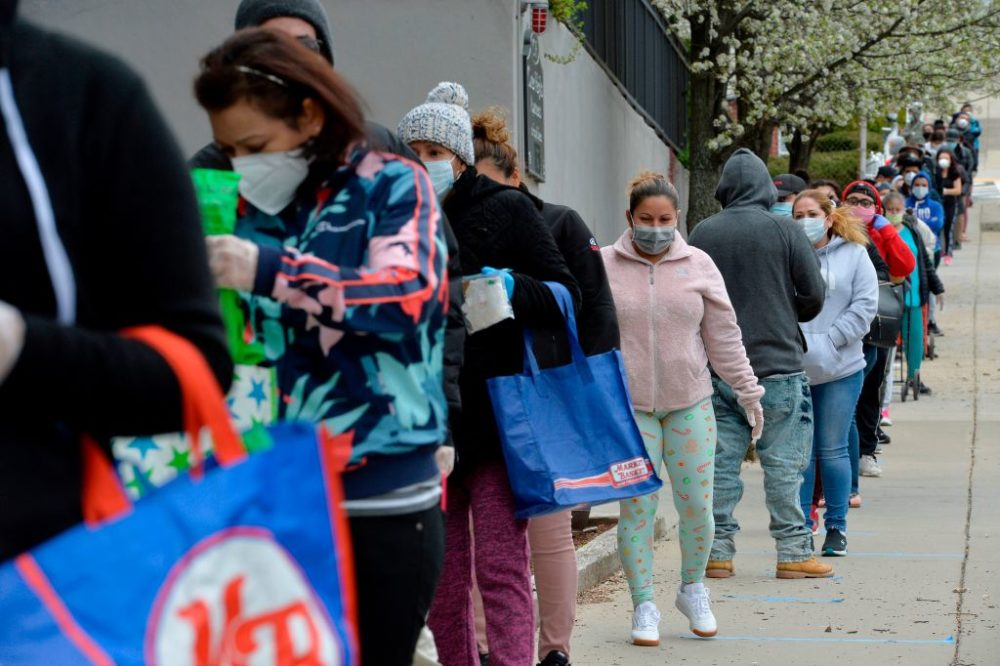 Hundreds of people line up to receive food and goods distributed by volunteers from the Chelsea Collaborative Inc. outside the Pan Y Cafe in Chelsea, Massachusetts on April 14, 2020. (Joseph Prezioso/ AFP via Getty Images)