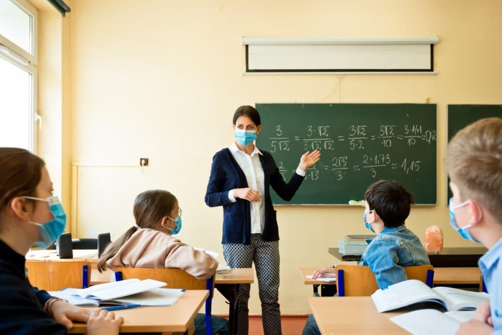 A teacher wearing a mask teaches mathematics. (Getty Images)