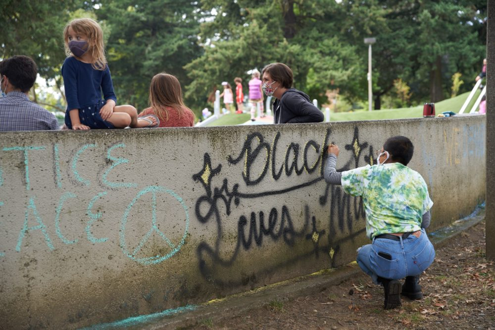 """Julia Mapilisan spray paints """"Black Lives Matter"""" on a wall as people gather at Lents Park in Portland, Oregon, on September 5, 2020, to mark the 100th day of protests denouncing police brutality and racism. (Allison Dinner/AFP via Getty Images)"""