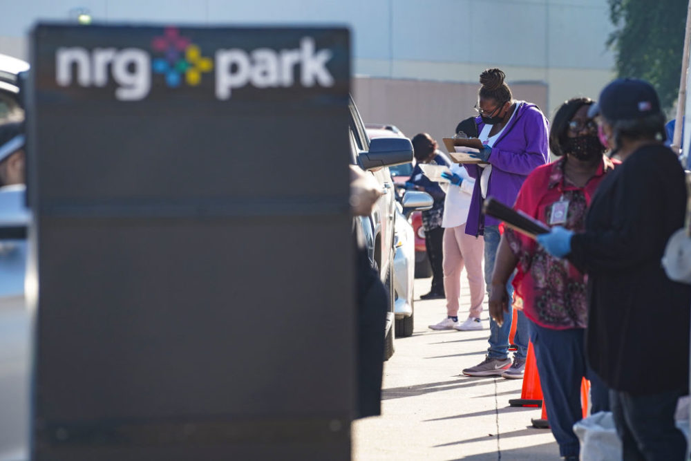 Election workers accept mail in ballot from voters at drive-through mail ballot drop off site at NRG Stadium on October 7, 2020 in Houston, Texas. Gov. Gregg Abbott  issued an executive order limiting each Texan county to one mail ballot drop-off site. (Go Nakamura/Getty Images)