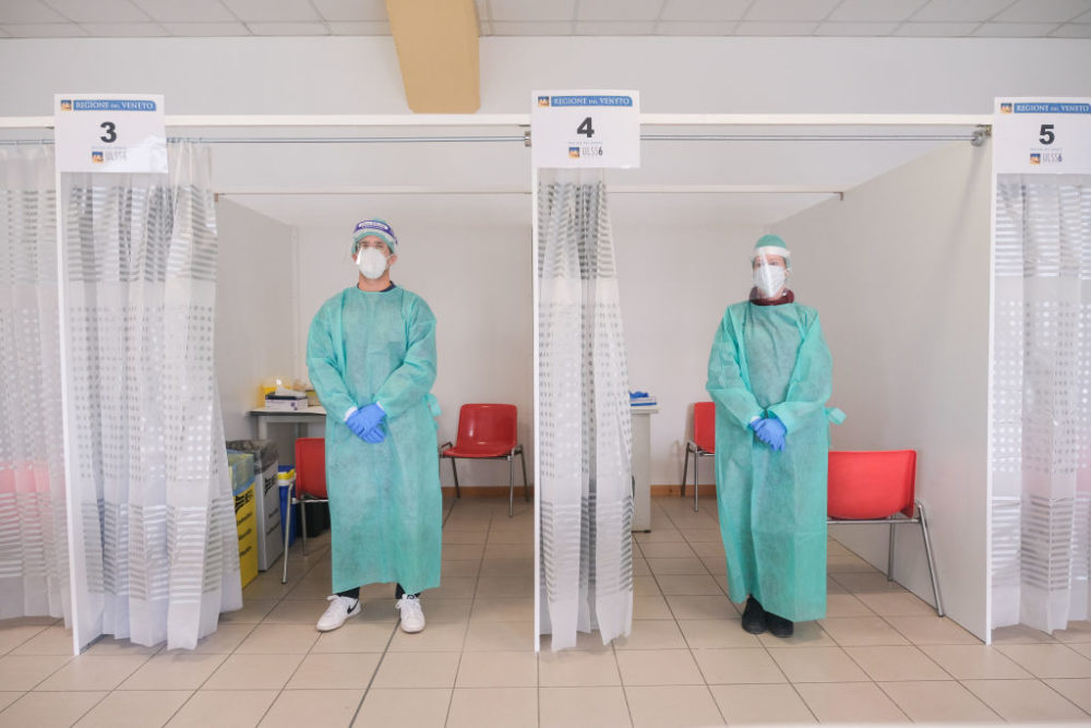Two doctors posing in front of the rooms where coronavirus swab tests are carried out. in Padua, Italy October 19, 2020. (Roberto Silvino/NurPhoto via Getty Images)
