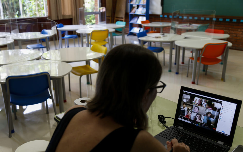 A teacher sits in an empty classroom while conducting an online class at Santa Maria school amidst the coronavirus pandemic on October 2, 2020 in Sao Paulo, Brazil. (Miguel Schincariol/Getty Images)