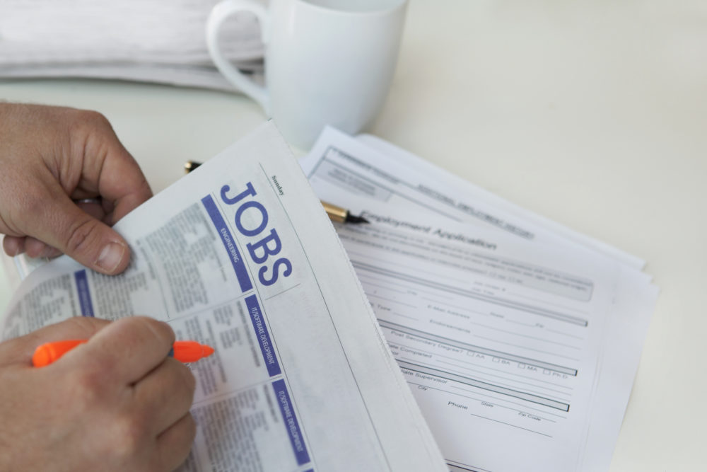 A person browses job postings in a newspaper. (Getty Images)