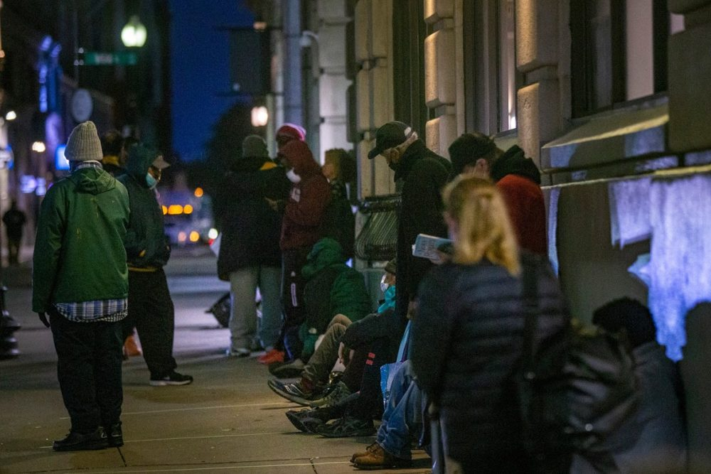People experiencing homelessness stand in line outside St. Francis House in Boston, in October 2020, waiting for the day shelter to open. (Jesse Costa/WBUR)