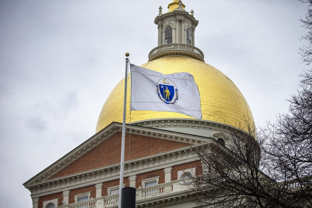 The Massachusetts state flag flies in front of the State House. (Jesse Costa/WBUR)