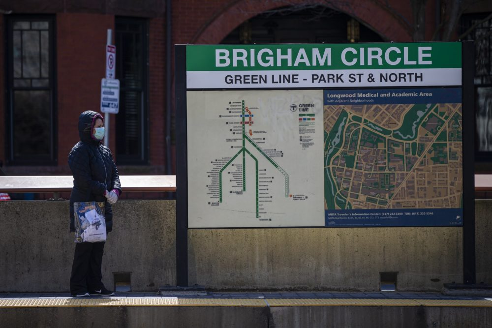 A woman wearing a mask waits for an MBTA Green Line train at Brigham Circle Station. (Jesse Costa/WBUR)