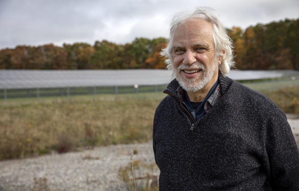 Gerry Palano, an alternative energy specialist at the Massachusetts Department of Agricultural Resources, with an array of solar panels in a field behind him. (Robin Lubbock/WBUR)