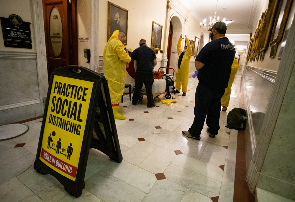 Staff members from Clean Harbors, a company that offers COVID-19 decontamination and disposal services, pulled on yellow jumpsuits before entering the House speaker's office. (Sam Doran/SHNS)
