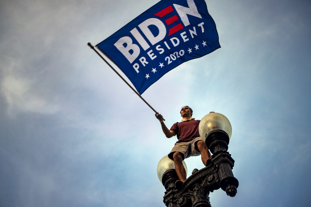 Tristan Homewood waves a Biden campaign flag as he stands on a street lamp on the corner of Boylston and Charles Streets to celebrate Joe Biden's presidential victory. (Jesse Costa/WBUR)