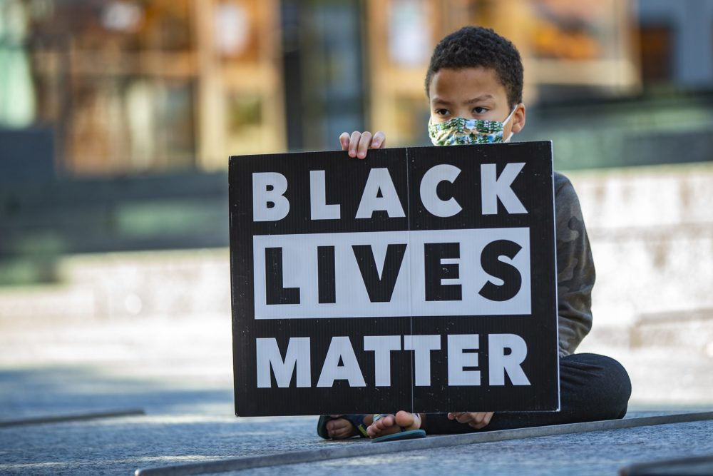 10-year-old Marcus Bilodeau holds a Black Lives Matter sign during the What this Win Means for Black Lives rally at City Hall Plaza. (Jesse Costa/WBUR)