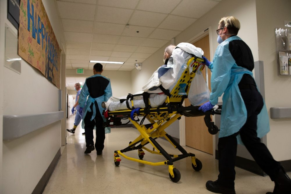 An EMT transfers a patient out of an acute care COVID unit at Harborview Medical Center in Seattle in May. As a second surge begins in Massachusetts, hospitals are planning to pool resources to manage an increase in patients. (Karen Ducey/Getty Images)